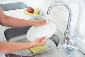 Person washing dishes in sink