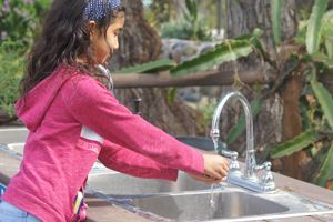 Girl washes hands at Olivewood Gardens