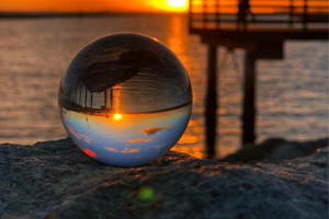Glass orb reflecting sunlight and water