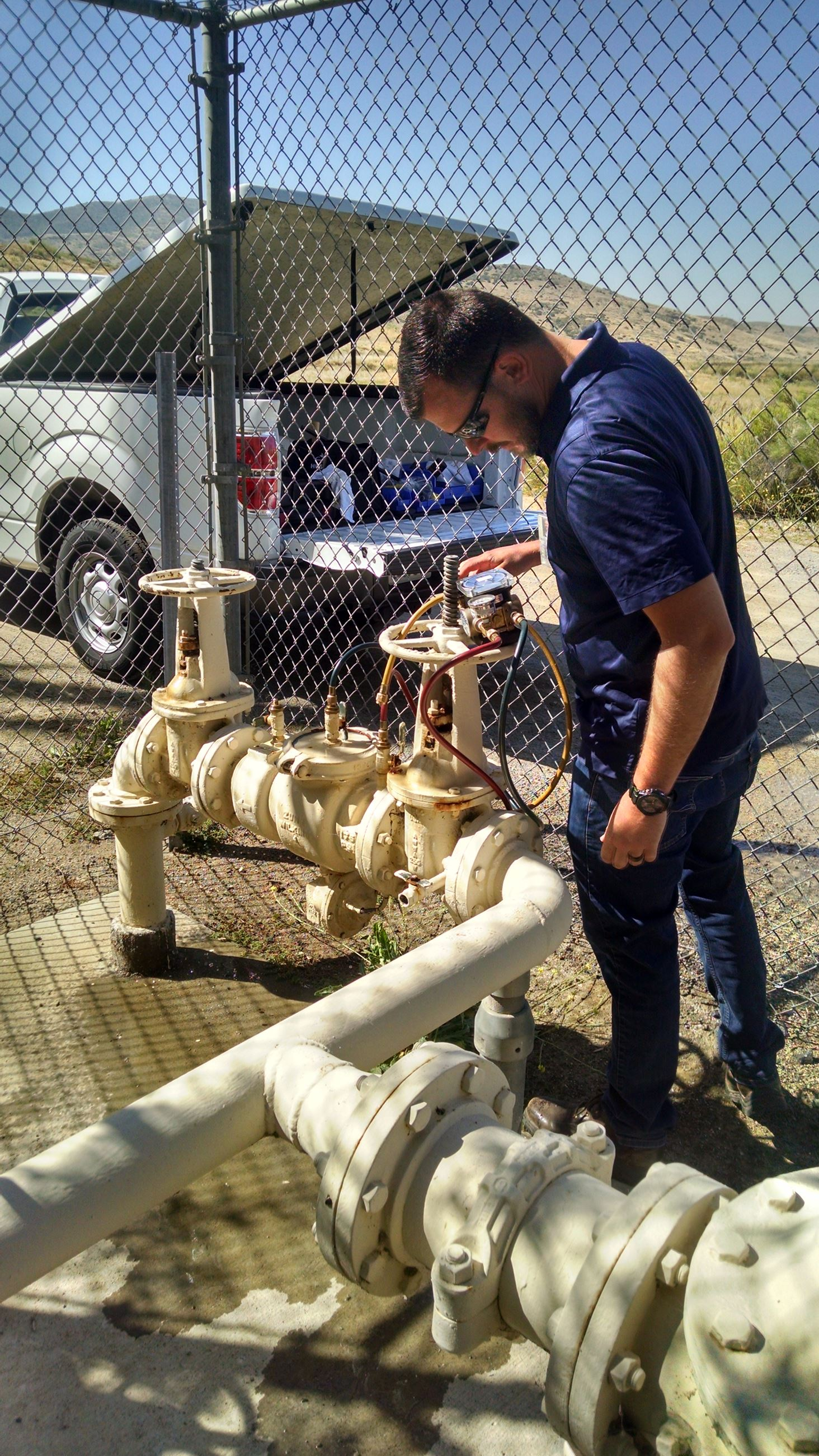 SWA employee reading pressure gauge on backflow prevention assembly