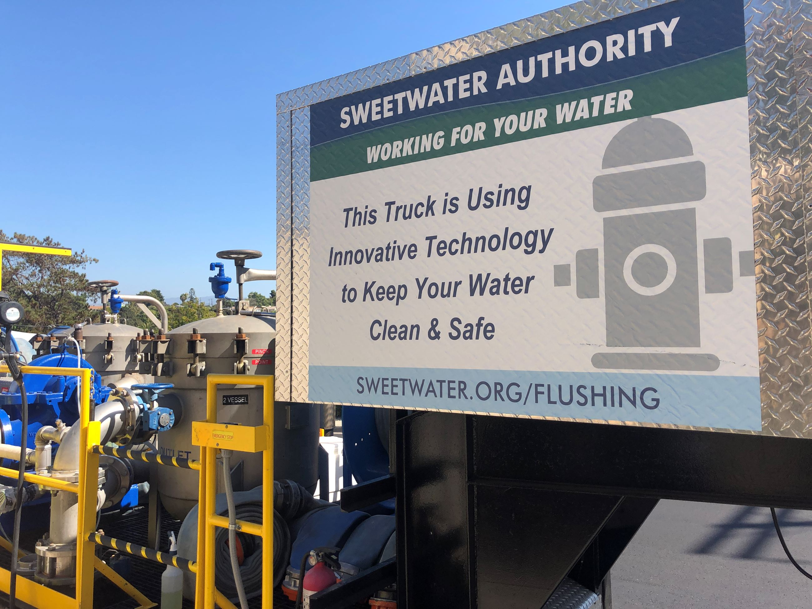 Sign on flushing truck about water-saving tech